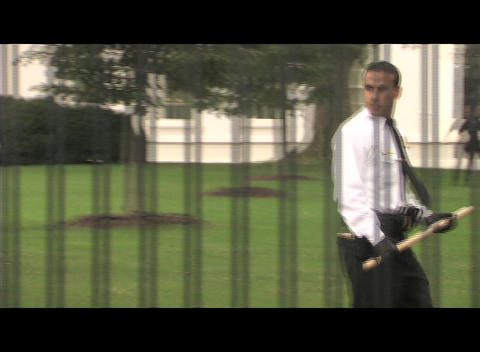 Pan-right shot of a Latino security guard with a bat behind the White House gates Footage