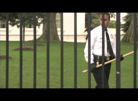 Pan-right shot of a Latino security guard with a bat... Stock Video Footage