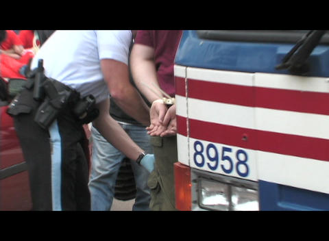 Zoom-in on the handcuffs on an anti-Iraq-war protestor... Stock Video Footage