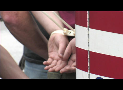 Zoom-in on the handcuffs on an anti-Iraq-war protestor arrested at a rally in Washington DC Footage