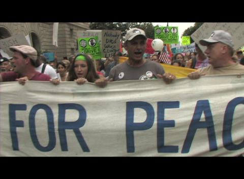 Hand-held shot of anti-Iraq-war protestors in Washington DC carrying a banner for peace Footage
