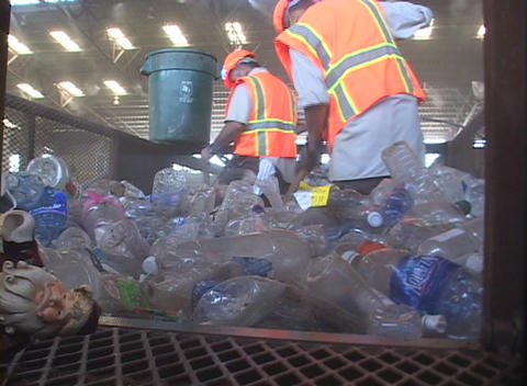 Workers at a recycling center sweep up plastic bottles Stock Video Footage