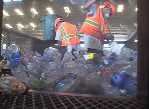 Workers at a recycling center sweep up plastic bottles Footage