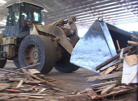 A loader moves piles of recyclable materials in a... Stock Video Footage