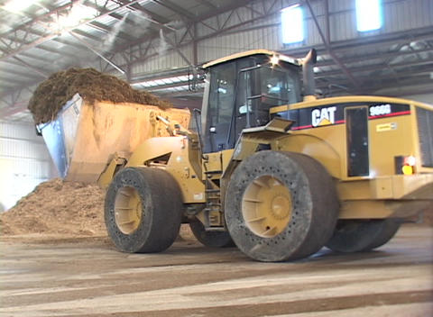 A bulldozer shovels debris into a large container truck... Stock Video Footage