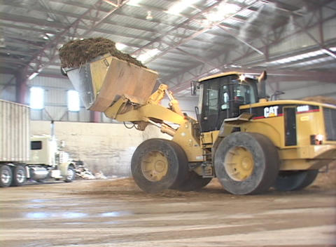 A bulldozer shovels debris into a large container truck at a recycling center Footage