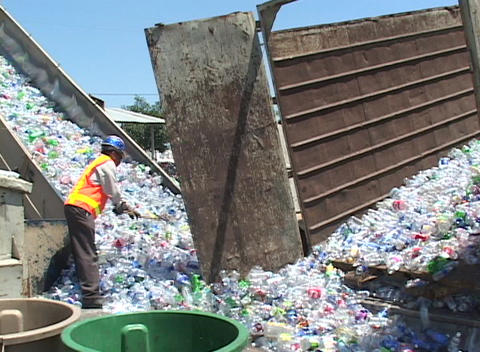 Thousands of plastic bottles are unloaded at a recycling center Footage