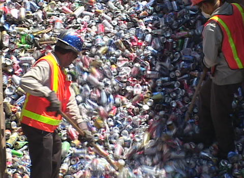 Workers rake aluminum cans at a recycling center Footage