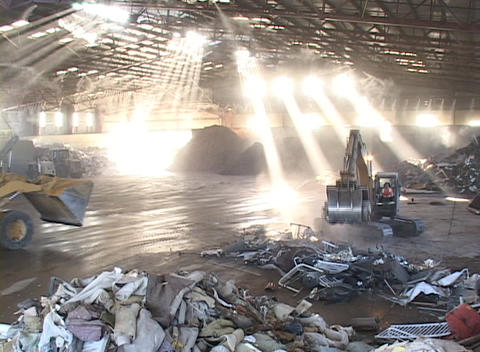 Large tractors and shovels work inside a recycling center Footage