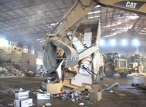 The claw arm of a large shovel grabs garbage from a truck in a recycling center Footage