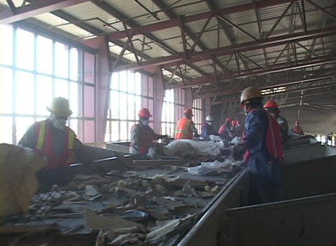 Workers at a recycling facility sort large objects from a conveyor belt Footage