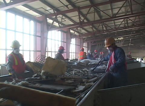 Workers at a recycling facility sort large objects from a... Stock Video Footage