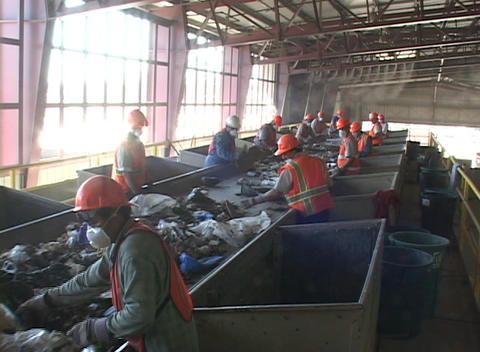 Workers sort garbage at a recycling plant Stock Video Footage