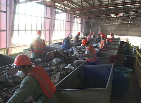 Workers sort garbage at a recycling plant Footage