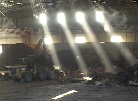 Bulldozers move recycling center materials through light beams Footage