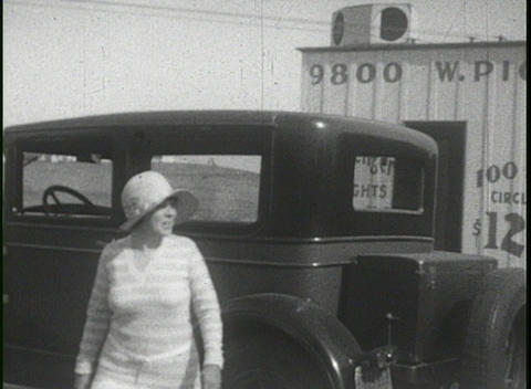 People mill around 1930's cars and an old biplane in this... Stock Video Footage