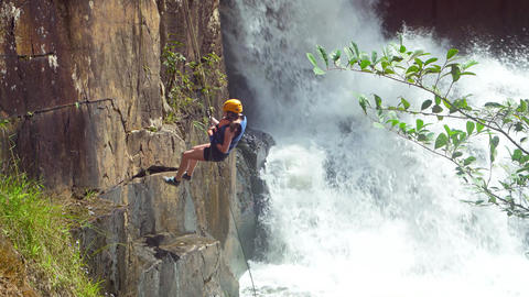 Tourist rappels down the sheer cliff into the river below Datanla Waterfall Footage