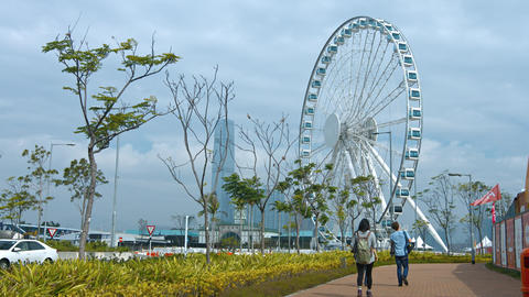 Tourists strolling toward the enormous Ferris wheel in Hong Kong. China Live Action