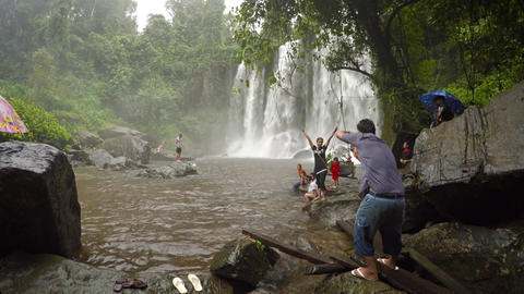 Tourists pose for pictures at base of a waterfall at Phnom Kulen National Park Footage