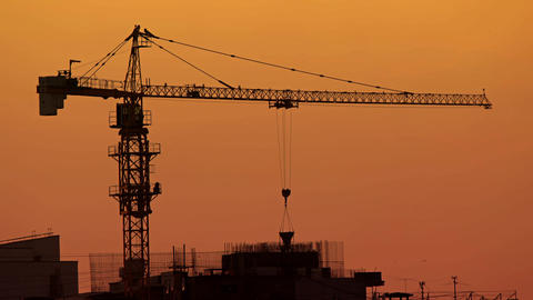 Laborer Working with Crane Mounted Concrete Bucket at Sunset. Video 4k Footage