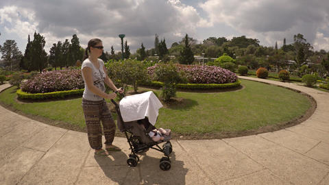 Mother pushes a baby stroller around Flower Garden Park in Dalat. Vietnam Footage