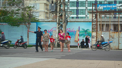 Traffic cop assisting pedestrians to cross a busy street in Nha Trang. Vietnam Footage