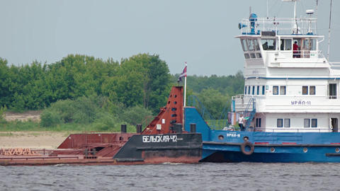 Tug boat pushing an industrial barge on the Volga River. 4k UltraHD footage Footage