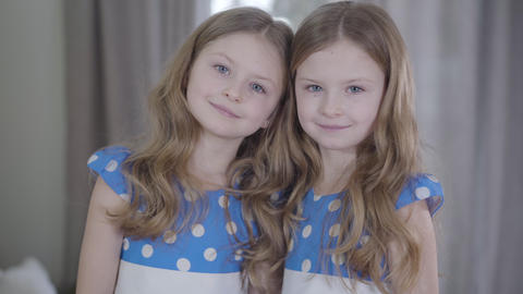 Camera approaching to friendly twin sisters looking at camera. Portrait of Live Action