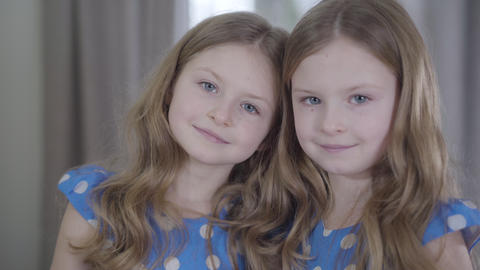 Camera moving away from faces of charming little twin sisters smiling at camera Live Action