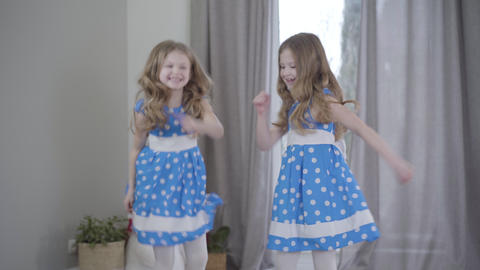 Joyful pretty Caucasian girls in elegant blue dotted dresses jumping and Live Action