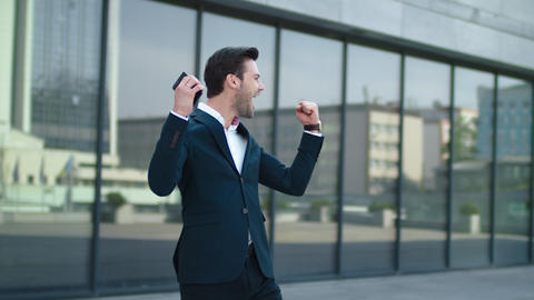 Closeup man using smartphone at street. Businessman celebrating victory outdoor Live Action