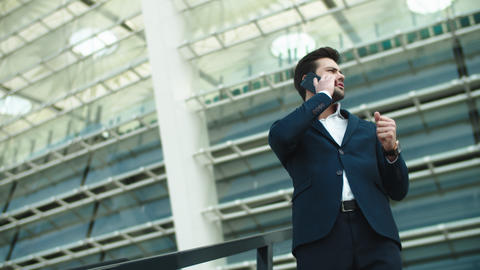 Closeup businessman talking smartphone. Businessman smiling with phone outdoors Live Action
