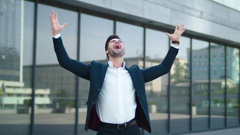 Closeup businessman spinning at street. Man raising hands above at city center Live Action