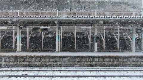 Japan railway window. Departing from a snowy station Live Action