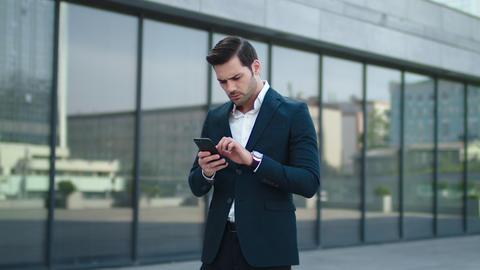 Closeup businessman reading bad news at street. Businessman using smartphone Live Action