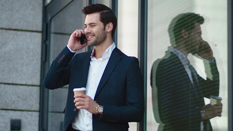 Closeup businessman smiling outdoors. Businessman drinking take away coffee Live Action