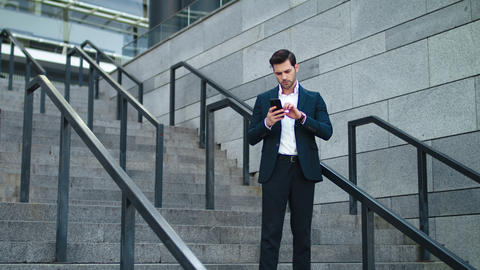 Business man using phone at stairs outdoor. Businessman smiling at stairs Live Action