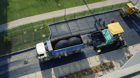 Timelapse. Constructions workers working on road. Asphalt paver applying hot Live Action