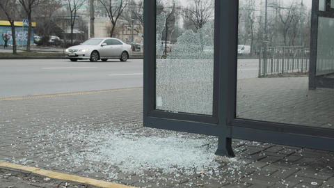Broken glass at a public transport stop. Vandalism in the city Live Action