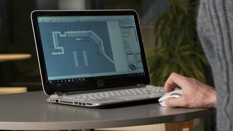 Male person is working on architectural designs using a laptop. Architect Live Action
