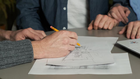 A designer draws a sketch of a kitchen design in a meeting with a young couple Live Action