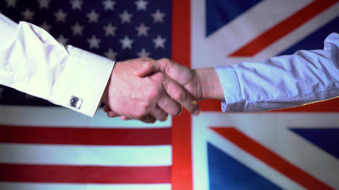 Handshake between the USA and the UK against the background of the flags of the Live Action