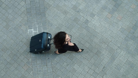 Top view woman walking with suitcase outdoor. Woman putting off sunglasses Live Action