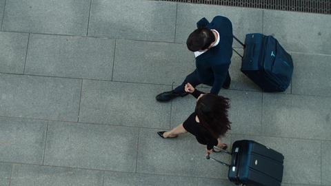 Top view couple walking with suitcases. Business couple talking together Live Action