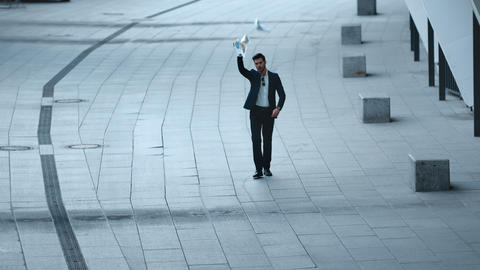 Businessman reading documents at street. Man throwing papers in slow motion Live Action