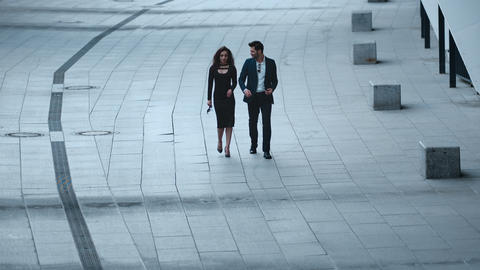 Business couple talking in stylish clothing. Business couple walking at sidewalk Live Action