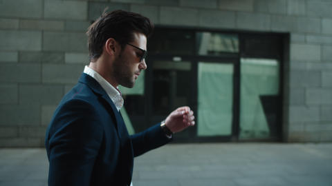 Portrait man wearing sunglasses at street. Man turning head in suit outside Live Action