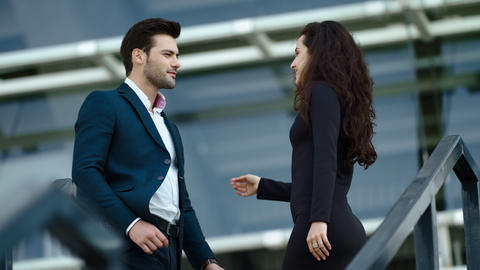 Close up young couple meeting at street. Business man and woman smiling outdoors Live Action