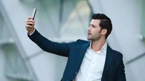 Portrait male entrepreneur taking selfie photo on mobile phone at city street Live Action