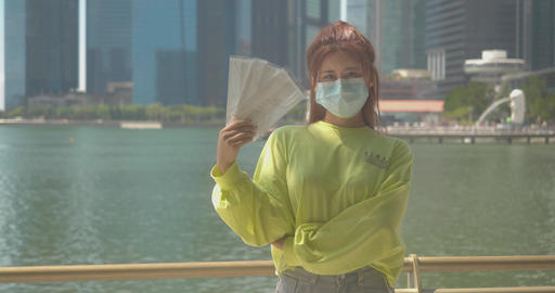 Asian Chinese girl wearing a surgical face mask and holding extra face masks in her hands to protect Live Action